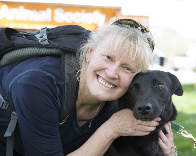 woman smiling with a black dog