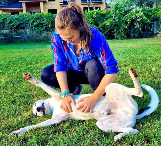Woman giving a dog a belly rub